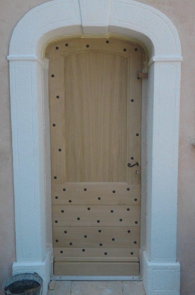 Porte menuisée rustique en anse de panier en chêne massif, clous mariniers. Lasure incolore