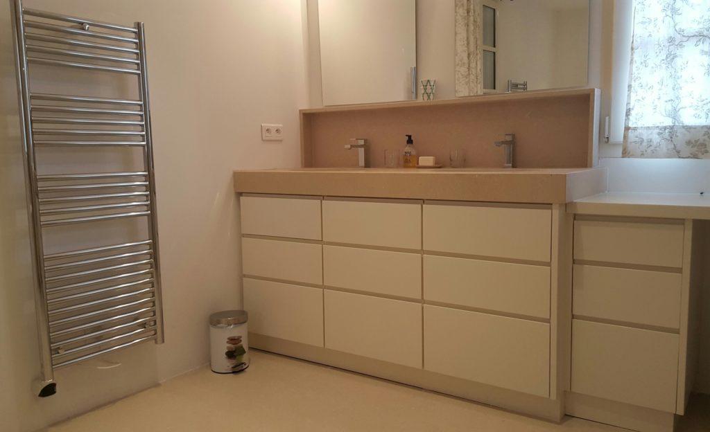 Meuble de salle de bain à tiroirs, façades en medium laqué avec prises de main intégrées. Plan en pierre
