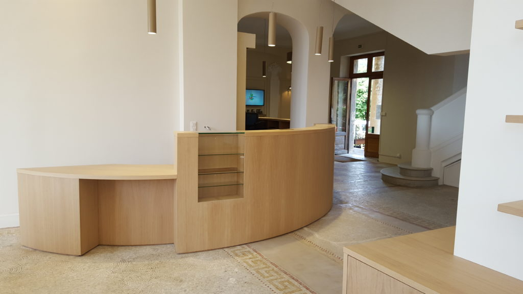 Banque d'accueil : corps panneaux cintrés replaqué chêne, plan en chêne, verni mat, vitrine en verre intégrée. Emplacement spécial PMR
