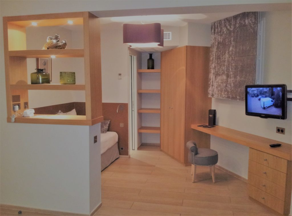 Aménagement chambre d'hôtel : dressing en placage chêne, plan de bureau et étagères à fixation invisibles. Verni satiné