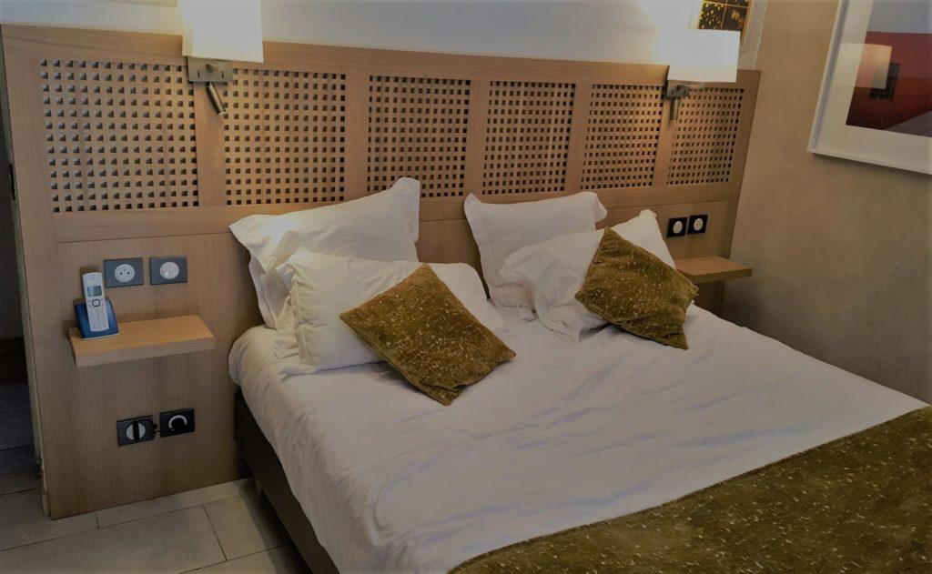 Tête de lit en placage chêne, partie haute en caillebottis de chêne massif. Tablettes de lit fixation invisible.